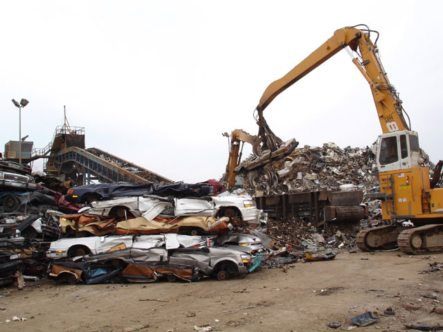 When it's time to shred the crushed cars for scrap metal, they are loaded onto a conveyer and fed into the shredder